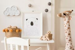 Cute interior of kid room with baby accessories, toys and poster frame.