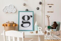 Cute interior of kid room with poster frame, baby accessories and toys.