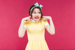 Cute irritated pinup girl closed her ears by fingers Stock Photos