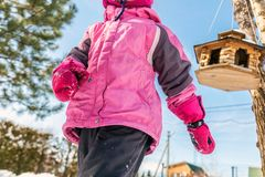 Cute ittle caucasian girl in sport winter jacket having fun playing outdoors with snow. Bird feeder on tree on background. Winter. Vacation and holidays concept royalty free stock images