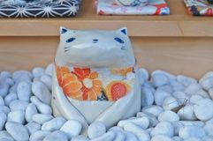 Cute Japanese ceramic cat doll with orange flower clothes. Wrapping around stock photography