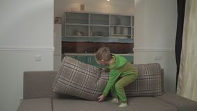 Cute jouful boy in green pajamas jumps on the sofa at home. Child grabs pillow and throws in on the floor. Happy. Cute small boy in green pajamas jumps on the stock video