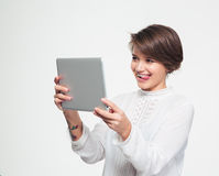 Cute joyful girl showing tongue and making selfie using tablet Royalty Free Stock Photography