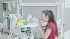 Playful mother making baby laugh during feeding stock footage