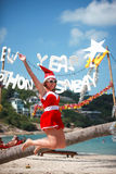 Cute joyful woman jumps in red dress and santa hat on exotic tropical beach. Holiday concept for New Years Cards. Koh Royalty Free Stock Images