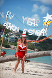 Cute joyful woman jumps in red dress, sunglasses and santa hat on exotic tropical beach. Holiday concept for New Years Royalty Free Stock Photos
