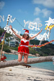 Cute joyful woman jumps in red dress, sunglasses and santa hat on exotic tropical beach. Holiday concept for New Years Stock Images