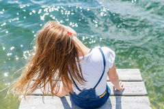 Cute joyfull teenage girl sitting on small dock and looking at the river. Royalty Free Stock Images