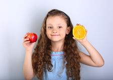 Cute joying smiling kid girl with curly hair style holding citru Stock Images
