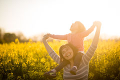 Cute joyous kid girl riding on shoulders of her mother Stock Photos
