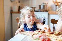 Free Cute Kid Are Eating And Tasting Italian Homemade Pizza In Cozy Home Kitchen. Stock Image - 159366191
