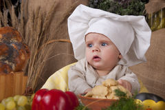 Cute kid as a chef. Cute kid in a chef's hat sitting Stock Photo