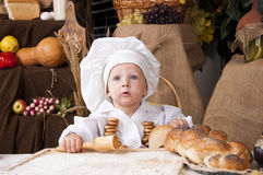 Cute kid as a chef. Cute kid in a chef\'s hat looking Royalty Free Stock Image