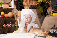 Cute kid as a chef. Cute kid in a chef\'s hat looking and showing somewhere Royalty Free Stock Photo