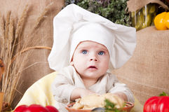 Cute kid as a chef. Cute kid in a chef\'s hat cooking Royalty Free Stock Photo