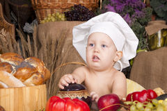 Cute kid as a chef. Cute kid in a chef\'s hat cooking Royalty Free Stock Images