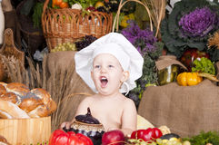 Cute kid as a chef. Cute kid in a chef\'s hat cooking and smiling Royalty Free Stock Image
