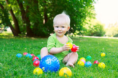 Cute kid baby boy sitting on grass playing with balls Royalty Free Stock Photo