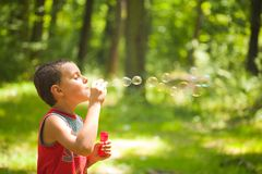 Cute kid blowing soap bubbles Royalty Free Stock Photos