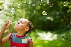 Cute kid blowing soap bubbles Stock Photo