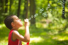 Cute kid blowing soap bubbles. Cute kid blowing bubbles outdoors, in the forest in a beautiful sunny afternoon Royalty Free Stock Photography