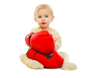 Cute kid in boxing gloves sitting on floor Royalty Free Stock Image