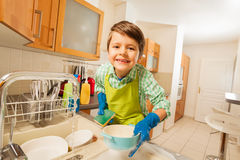Cute kid boy doing the dishes in rubber gloves. Portrait of cute kid boy doing the dishes in rubber gloves in the kitchen stock photography