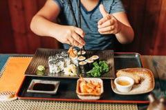 Cute kid boy eating sushi. In asian restaurant stock photos