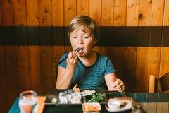 Cute kid boy eating sushi stock photo