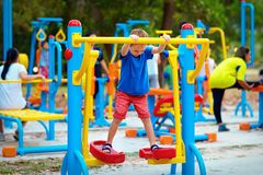 Cute kid, boy exercising on sport ground with other people on background Stock Image