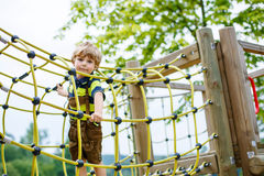 Cute kid boy having fun with climbing on children playground Stock Images