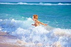 Cute kid boy having fun in sea surf Stock Photos
