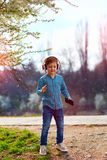 Cute kid boy with headphones listens to the music and dancing in blooming park Stock Image