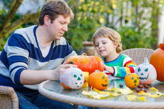 Cute kid boy and his father  making jack-o-lantern for halloween. Cute kid boy and his father making jack-o-lantern for halloween in autumn garden, outdoors Stock Photography