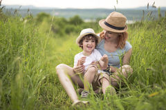 Cute kid boy with his mother on a summer meadow Royalty Free Stock Photography