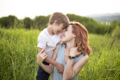 Cute kid boy with his mother on a summer meadow Royalty Free Stock Photo