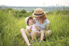Cute kid boy with his mother on a summer meadow Stock Images