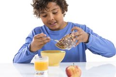 Cute kid boy i blue T-shirt Pouring cereal into a white ceramic bowl isolated on white. Cute kid boy Pouring cereal into a white ceramic bowl isolated on white royalty free stock photo
