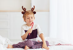 Cute kid, boy licking christmas candy in the winter morning Stock Image