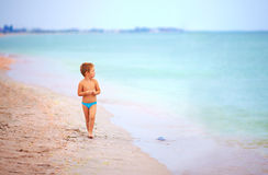 Cute kid boy looking into the distance, beach Stock Images