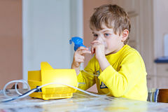 Cute kid boy making inhalation therapy by the mask of inhaler Royalty Free Stock Photos