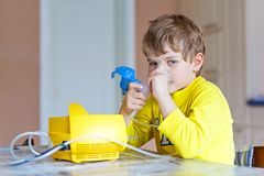 Cute kid boy making inhalation therapy by the mask of inhaler royalty free stock photography