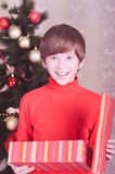 Cute kid boy open christmas present in room Stock Image