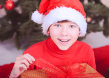 Cute kid boy open christmas present in room Stock Images