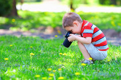 Cute kid boy photographing flowers Royalty Free Stock Images