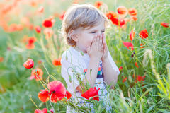 Cute kid boy with poppy flower on poppy field on warm summer day Stock Photo
