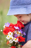 Cute kid boy with poppy flowers and other wild flowers in poppy Stock Photos