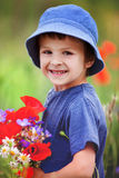 Cute kid boy with poppy flowers and other wild flowers in poppy Stock Images