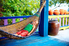 Cute kid, boy relaxing in hammock. Enjoying life on tropical island Royalty Free Stock Images