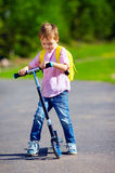 Cute kid boy riding a scooter on the road, summer outdoors Stock Image